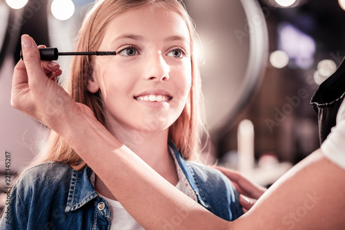 I like it. Charming kid expressing positivity and sitting in special chair while doing make-up