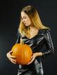 Beautiful young woman holding pumpkin for Halloween