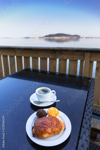 Wall mural Coffee cup and croissant on the table by the sea