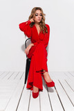 Fashion model on a white background, curly model in a red jumpsuit, fashion portrait