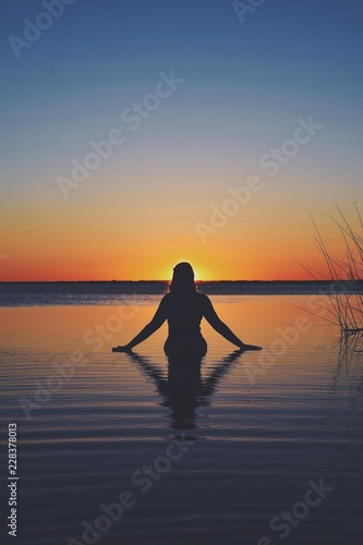 Woman in the sea while the sun sets