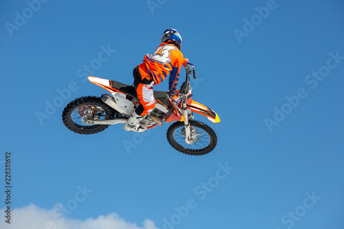 racer on a motorcycle in flight, jumps and takes off on a springboard against the blue sky
