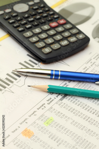 Business concept with a report, money and a calculator - 228390242