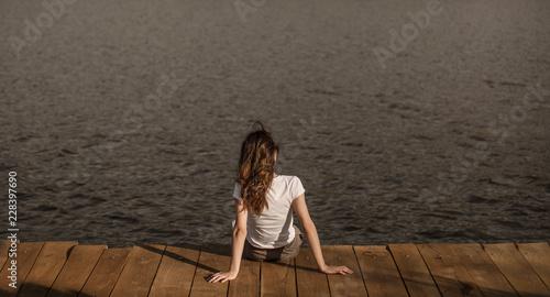 Sticker Anonymous female sitting on pier