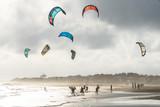 un groupe de kitesurf en bord de plage avec un ciel d'automne - 228398039