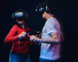 Happy friends playing video games wearing virtual reality glasses with controllers.