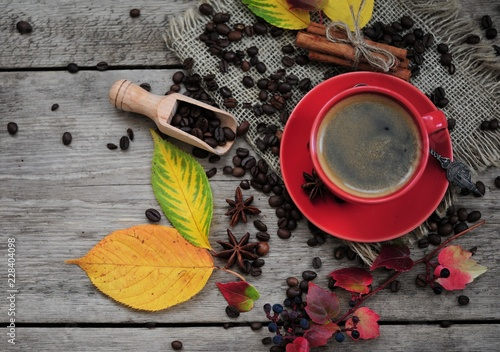 Wall mural cup of coffee with cinnamon and autumn leaves on an autumn background