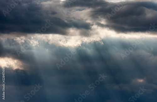 Foto Murales Dramatic dark and light cloudy sky with rays of sunlight