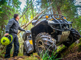 A man in an all-terrain vehicle. Forest. ATV. Leisure. A man goes on the road on the ATV. The traveler holds a helmet in his hands. Off-road.