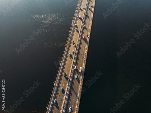 Fototapeta Aerial or top view from drone of concrete bridge with asphalt road or highway over big river with city car traffic, urban transportation