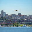 City lake and plane beneath clear blue sky