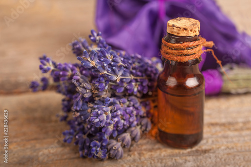 Essential lavender oil with a lavender flower on a rustic background - 228436629