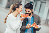 Couple eating pizza outdoors and smiling.
