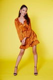 Isolate young tan Asian woman with long hair and orange dress. expressive facial over yellow background
