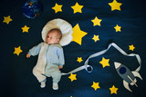 sleeping baby boy astronaut on a background of the sky with the space ship - 228451882