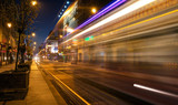 Light trails of a tram driving a street by night - 228454601