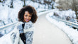 Cheerful stylish afro hair woman portrait under the snow at winter mountain road. Female wearing warm clothes and gloves.