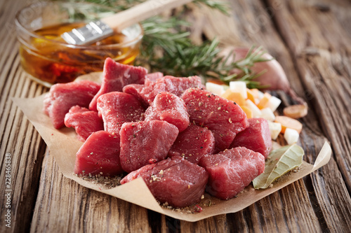 Leinwanddruck Bild Uncooked fresh diced seasoned meat with herbs