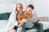 happy young couple reading newspaper together in bedroom - 228467210