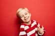 Quadro Lachender Junge vor einer roten Wand