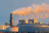 Pollution and smoke from the plant chimneys. View at sunset