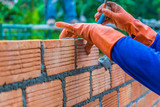 Hand of construction worker laying down brick wall one by one using mortar to connect and seal the gaps