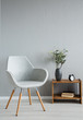 Stylish grey chair next to cabinet with vase and flowers in modern office interior, real photo with copy space on the empty wall