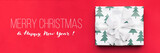 Christmas banner. Beautiful christmas gift isolated on red background. Wrapped xmas box. Gift wrapping concept.