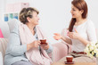 Young woman talking with grandmother drinking tea during meeting