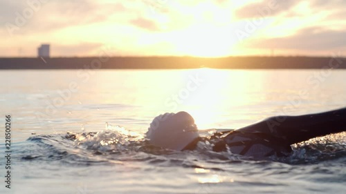 Tracking of young female athlete in cap and goggles swimming with freestyle stroke in blue lake at sunset