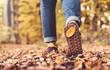 Leinwandbild Motiv Autumn concept, close up of shoe sole with yellow leaf on it