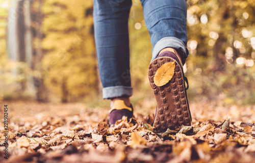 Leinwanddruck Bild Autumn concept, close up of shoe sole with yellow leaf on it