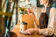 cropped image of waitress in apron holding disposable coffee cups and paper bag in cafe