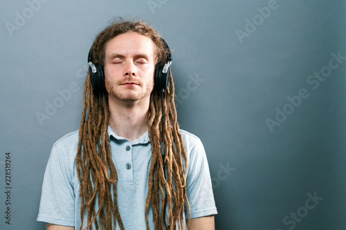 Man listening to headphones on a solid background - 228519264
