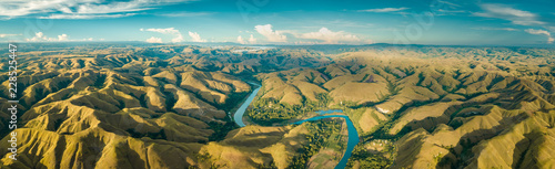 Panoramic view river, hills. Aerial drone shot. Indonesia. Spectacular landscape of Sumba island. Blue sky with white clouds . Beauty of wild untouched nature. - 228525447