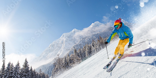 Skier skiing downhill in high mountains - 228526459