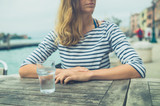 Woman at cafe table by the river - 228546420