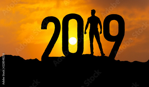 Leinwanddruck Bild man on mountain is greeting 2019 with power and confidence