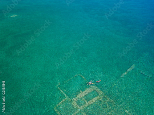 Aerial drone bird's eye view photo of tourists snorkeling above old Sunken City of Epidauros, Greece