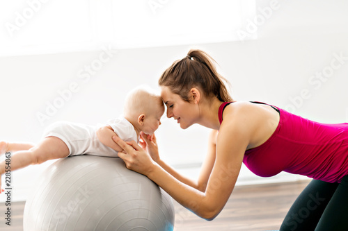 A Portrait of beautiful young mother in sports wear with her charming little baby in training session - 228554863