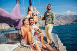 Smiling friends sailing on yacht. Vacation, travel, sea, friendship and people concept - 228572657