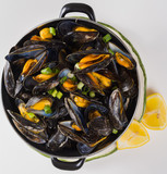 Black pan with cooked with green onion, parsley marinated high quality mussels top view - 228585013
