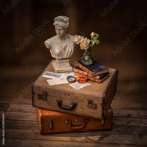 Still life with vintage suitcase, old letters, books and bust © marina