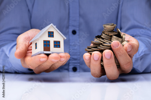 Man Holding House Model And Coins - 228599646