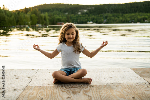 Obraz na płótnie child girl Yoga relax in pier at the sunset