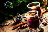 Christmas and New Year festive drink, hot mulled wine with cinnamon, cardamom, orange and anise star on background of green spruce branches and lights, rustic wooden table, selective focus - 228623620