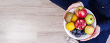 Girl holding white plate with apples, plums, kiwi and pomegranate. Healthy eating. Fitness and healthy lifestyle concept. Banner. Top view