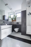 Mirror and flowers in white and grey bathroom interior with window and washbasin. Real photo