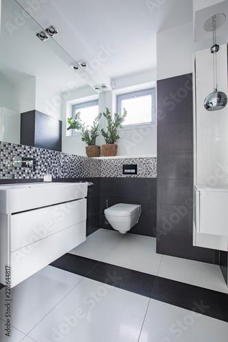 Lustro i kwiaty w białym i szarym wnętrzu łazienki z oknem i umywalką. Prawdziwe zdjęcie