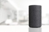Personal assistant loudspeaker on a white wooden shelf of a smart home living room. Empty copy space for Editor's text.